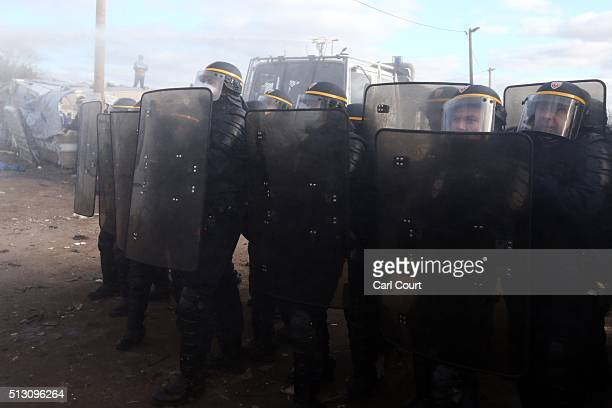 Police officers stand next to a water canon as it is fired at activists and migrants as part of the 'jungle' migrant camp is cleared on February 29...