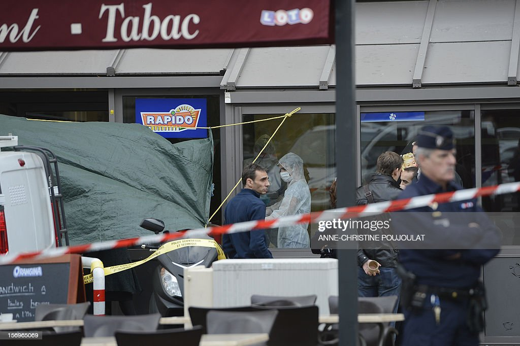 Police officers stand next to French forensic police officers looking for evidence on November 26, 2012 in Marseille, southeastern France, in front of a cigar store where a 47-year old man was shot...