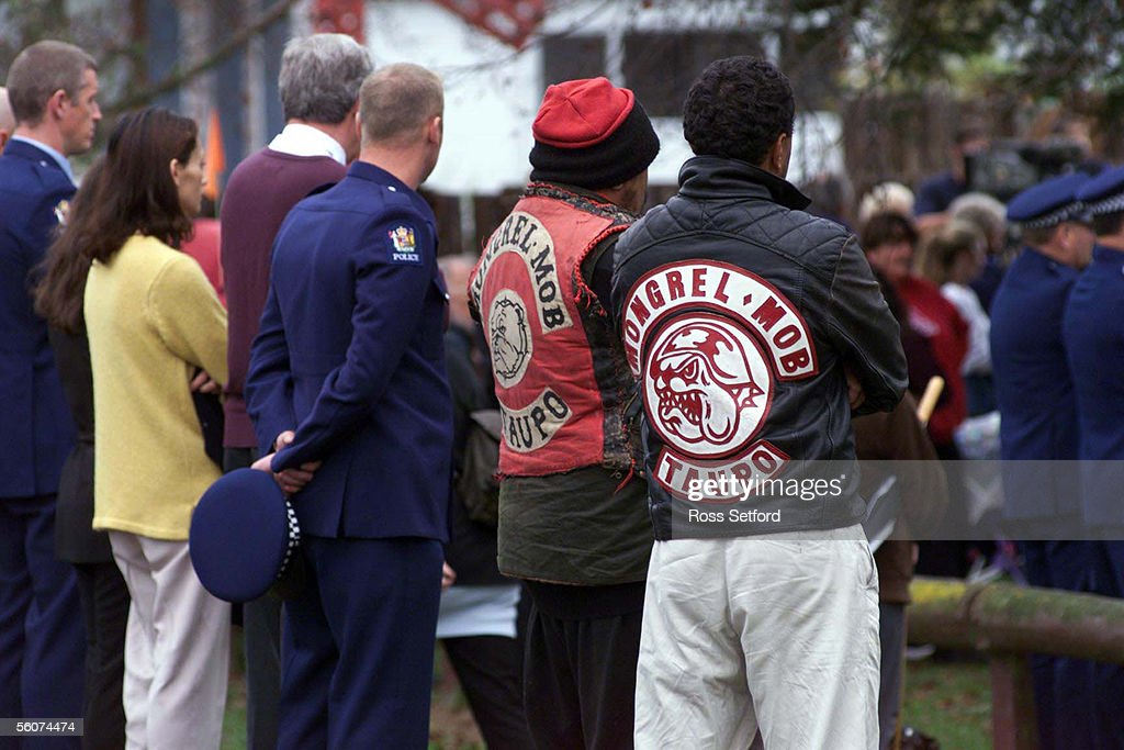 Police officers stand next to mongrel mob members : News Photo
