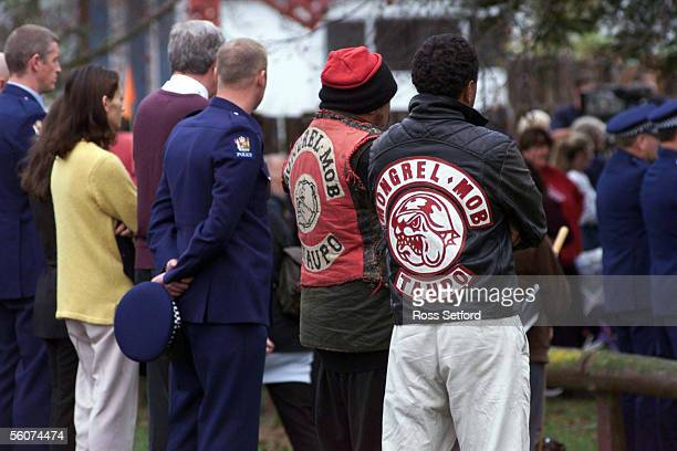 Police officers stand next to mongrel mob members outside the school where the funeral of murdered officer Murray Stretch was held today