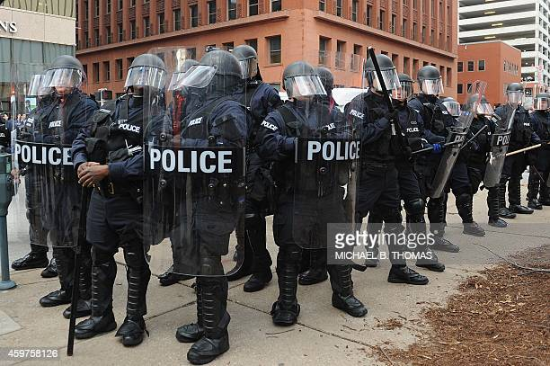 Police officers stand on alert after an arrest was made during a protest in downtown St Louis Missouri on November 30 2014 Demonstrators marched...