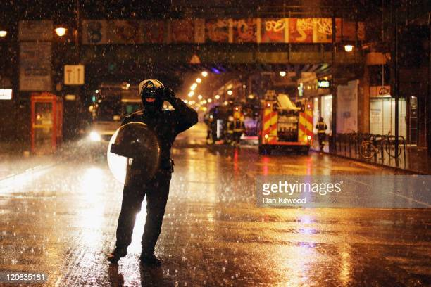 Police officers stand on Brixton High Street after looting broke out on August 8 2011 in London England Widespread rioting and looting took place...