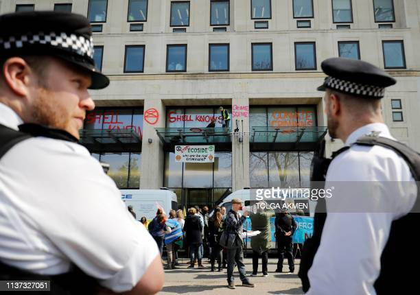 Police officers stand on duty as activists stand on the porch covering the entrance to the Shell Centre the UK offices of Royal Dutch Shell during an...