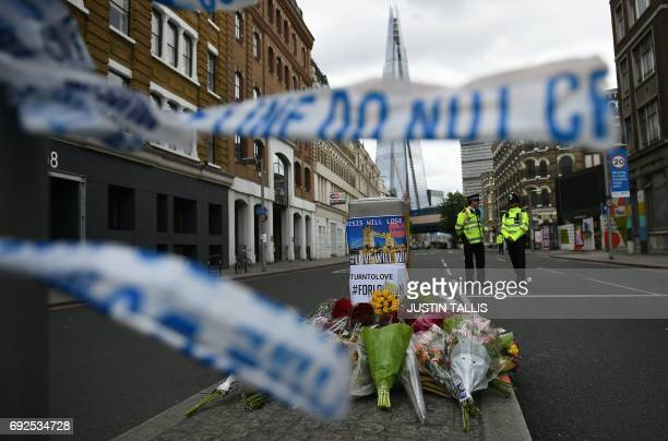 Police officers stand on duty at a cordon near Borough Market in London on June 5 as investigations continue following the June 3 terror attack...