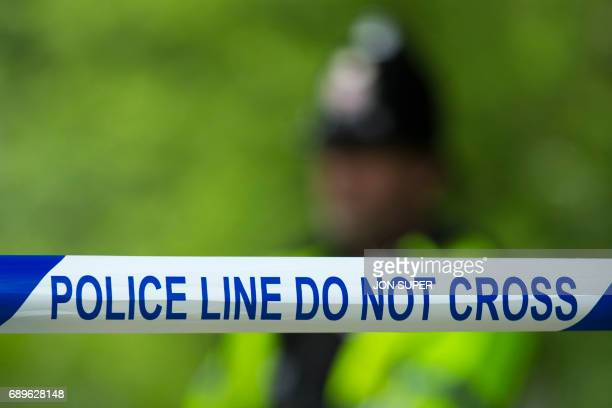 Police officers stand on duty by cordonedoff residential property on Montcliffe Crescent in the Whalley Range area of Manchester northwest England on...