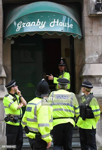 Police officers stand on duty follwing a raid at Granby House close to Manchester Piccadilly railway station in Manchester on May 24 as their...