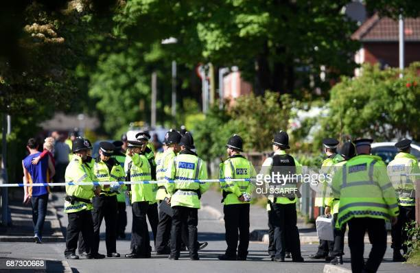 Police officers stand on duty on a cordonedoff road in Fallowfield Manchester in northwest England on May 23 as they search a resdiential property...