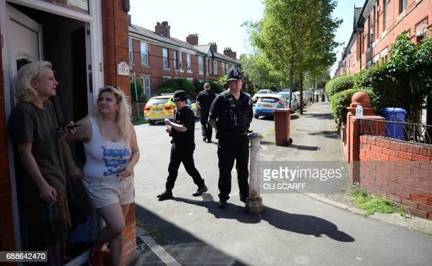 Police officers stand on duty on Dorset Avenue in Moss Side, Manchester, on May 26 following a raid on a residential property as their investigations...