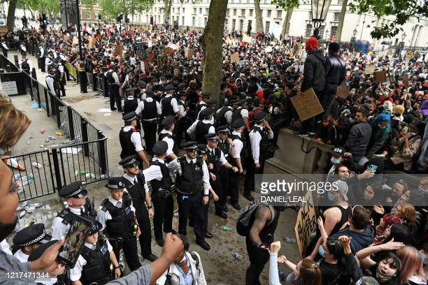 Police officers stand on duty outside the entrance to Downing Street as protestor's gather on Whitehall during an antiracism demonstration in London...