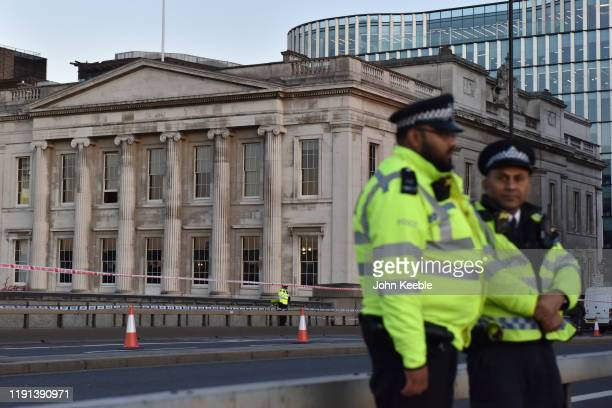 Police officers stand on London Bridge by Fishmongers' Hall early morning as the bridge is reopened after the recent stabbing attack on December 02...