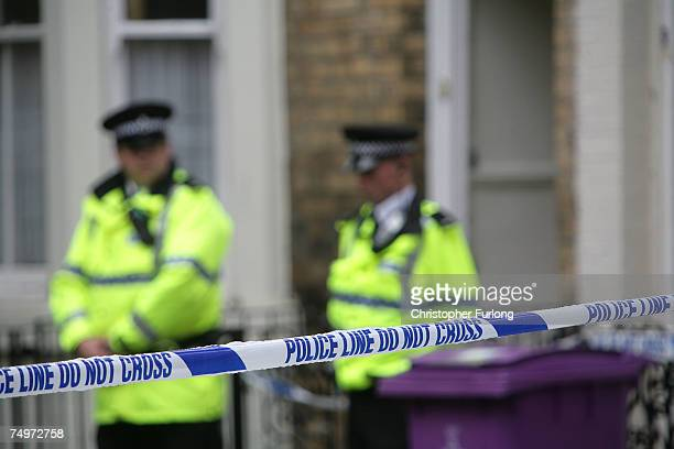 Police officers stand outside a house in Hatherley Street, after a raid searching for terror suspects on July 1, 2007 in Liverpool, England. Police...