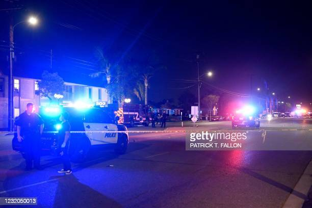 Police officers stand outside an office building were multiple people were killed in a shooting in Orange, California on March 31, 2021. -...