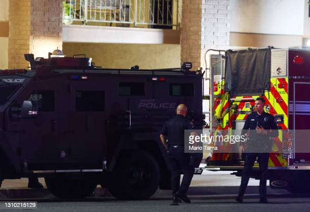 Police officers stand outside an office building where four people, including a child, were killed in a shooting on March 31, 2021 in Orange,...