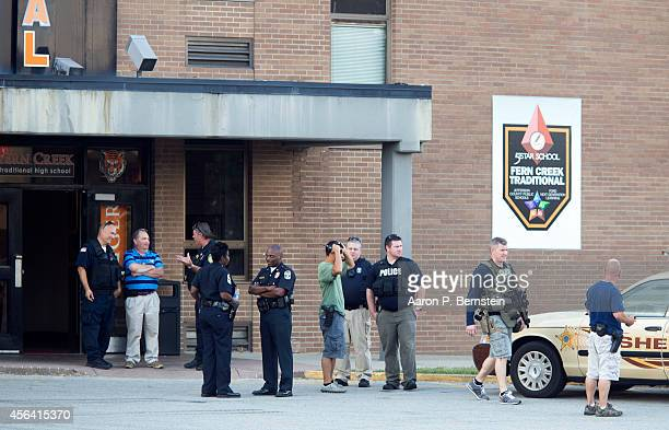 Police officers stand outside Fern Creek High School after a shooting incident September 30 2014 in Louisville Kentucky Police say a male suspect was...