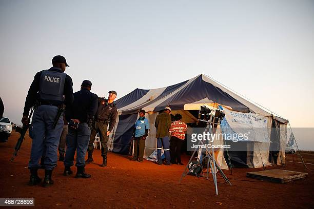 Police officers stand outside of a voting tent at a voting station at Bekkersdaal during the 2014 South African General Election on May 7 2014 in the...