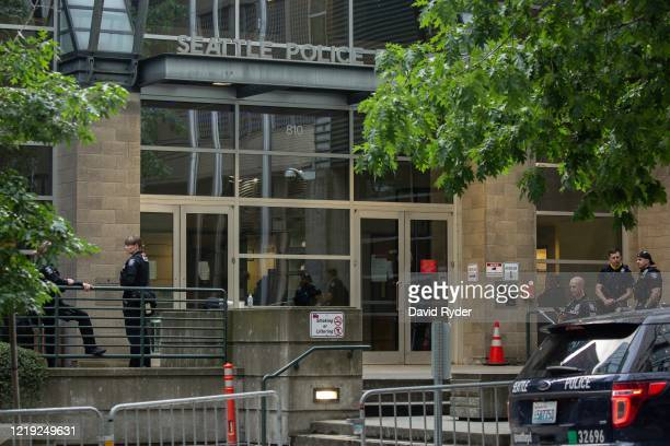 Police officers stand outside of the Seattle Police Departments West Precinct on June 10, 2020 in Seattle, Washington. The departments East Precinct...