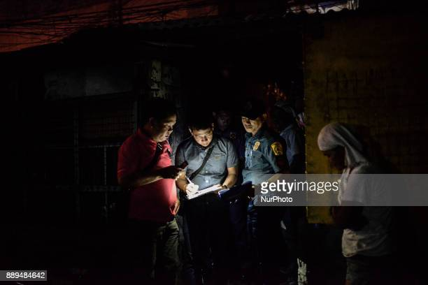 Police officers stand outside the home of an alleged drug user who was killed by unidentified assailants in Quezon city Metro Manila Philippines...