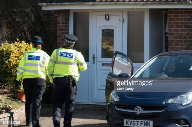 Police officers stand outside the home of Sergei Skripal in Salisbury who was found critically ill on a bench with his daughter on March 4 and were...