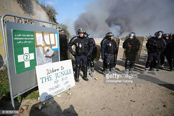 Police officers stand outside the notorious Jungle camp as migrants prepare to leave as the authorities start to demolish the site on October 26 2016...