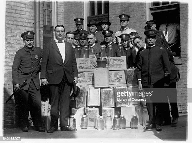 Police officers stand proudly with jars and crates of moonshine brewed illegally duirng the prohibition Washington DC
