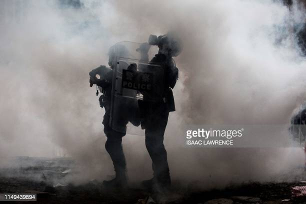 TOPSHOT Police officers stand surrounded by tear gas during a rally by protesters against a controversial extradition law proposal outside the...