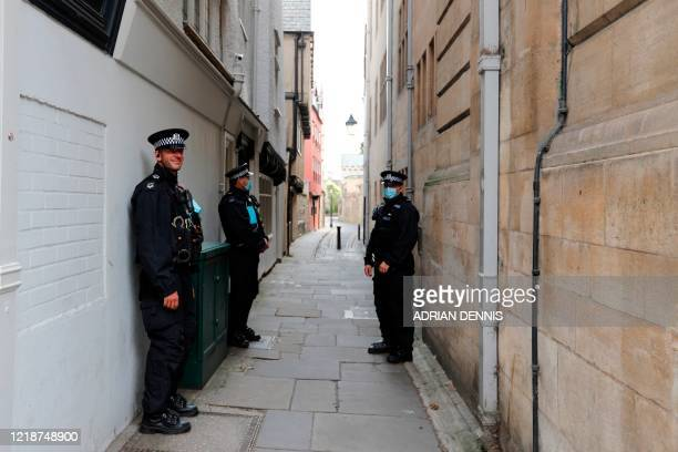 Police officers stand watch at the University of Oxford on June 9 2020 prior to a protest called by the Rhodes Must Fall campaign outside Oriel...
