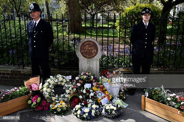 Police officers stand with floral tributes flanking a memorial stone at the spot where British police officer Yvonne Fletcher was killed during a...