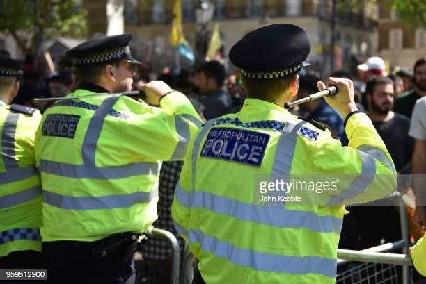 Police officers stand with their batons raised as anti-Erdogan protesters stage a demonstration outside Downing Street as Turkish President Recep...