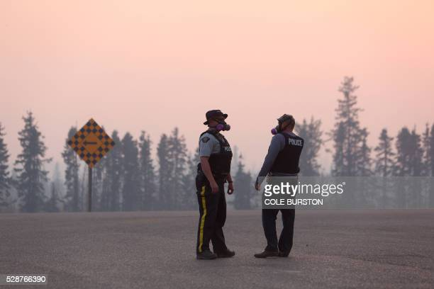 TOPSHOT Police officers standing in heavy smoke manage a road block on Highway 63 near Fort McMurray Alberta on May 6 2016 Canadian police led...