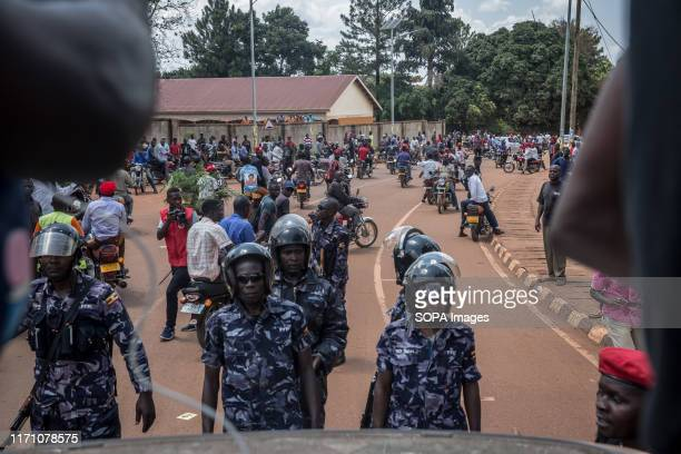 "Police officers stare down ""people power"" opposition supporters in Hoima Wine aka Robert Kyagulanyi, campaigned in Hoima ahead of a by-election. It..."