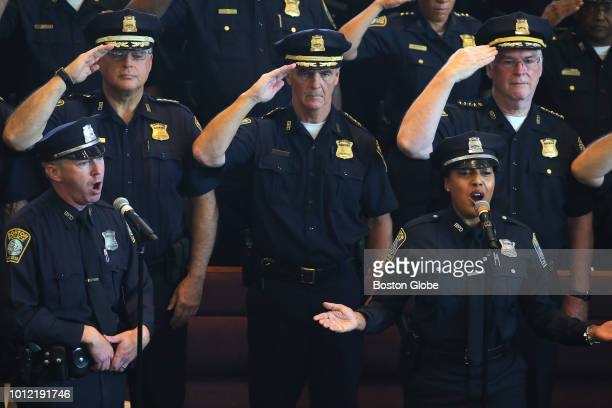 Police Officers Stephen McNulty and Kim Tavares sing the National Anthem during a ceremony in which William G Gross was sworn in as Boston's 42nd...