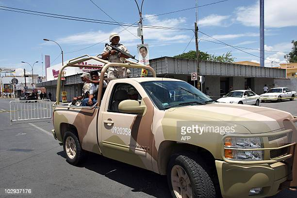 Police officers stnad guard at the scene of a car bomb attack on a main avenue in downtown Ciudad Juarez in northern Mexico on July 16 2010 An armed...