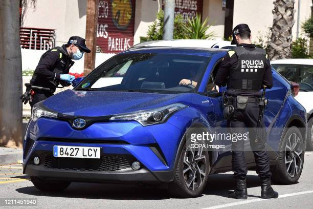 Police officers stop a driver at a checkpoint to ensure compliance with the rules during the Coronavirus lockdown crisis The Vendrell Local Police...