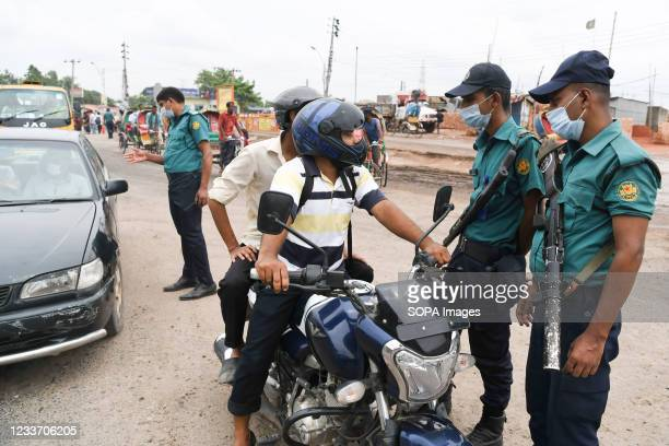 Police officers stop a motorcyclist at a checkpoint at the Gabtoli area during the covid-19 lockdown. Vehicle owners need to provide valid...
