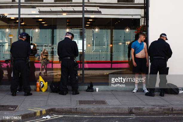 Police officers stop and search a trio of men close to the Westbourne Grove entry point to the 2019 Notting Hill Carnival in London England on August...