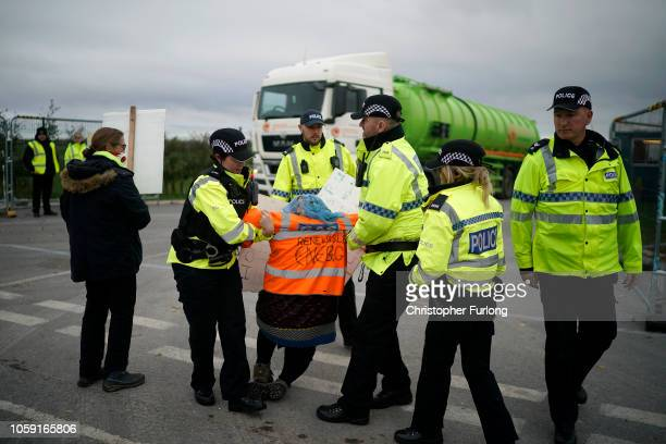 Police officers stop antifracking protesters attempting to halt a tanker lorry leaving the Preston New Road drill site where energy firm Cuadrilla...