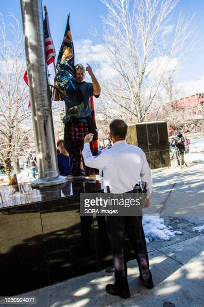 Police officers stop protestors from raising their own flag at the capital during the demonstration. Protesters gathered at the state's legislative...