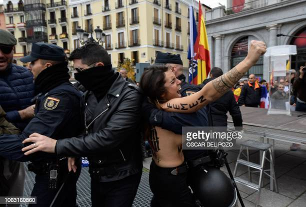 Police officers subdue a member of feminist movement Femen as she protests against a far right demonstration marking the anniversary of the death of...