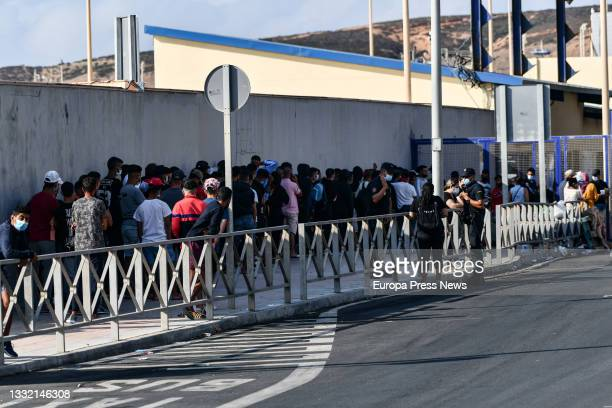 Police officers supervise hundreds of people, mostly Moroccans, queuing at the asylum office located at the Tarajal border separating Ceuta from...