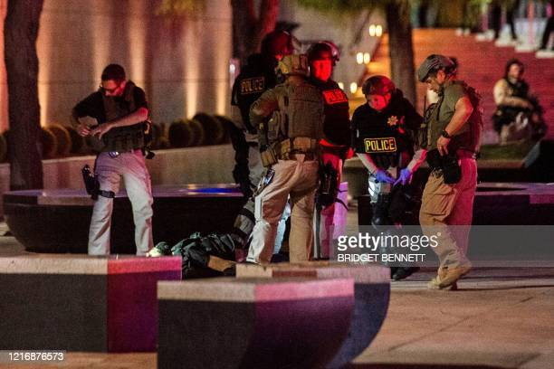 Police officers surround a person that was shot near the 300 block of South Las Vegas Boulevard, on June 1 in downtown Las Vegas, at the end of a...