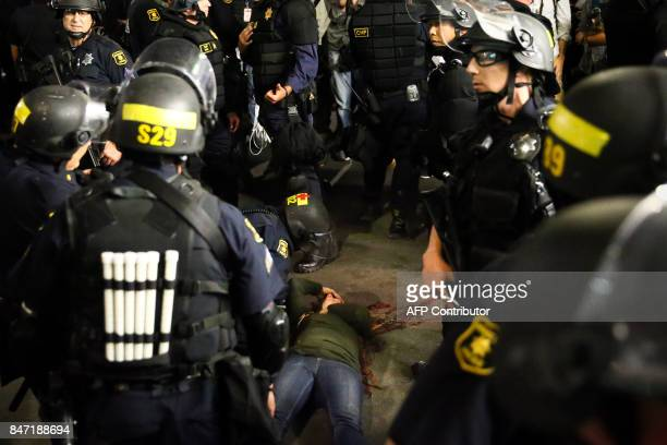 TOPSHOT Police officers surround a supporter of conservative commentator Ben Shapiro after she took a fall to the ground following a speech by...