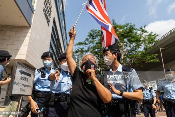 Police officers surround Alexandra Wong, a protester known as Grandma Wong who attended rallies over the course of Hong Kong's unrest last year,...
