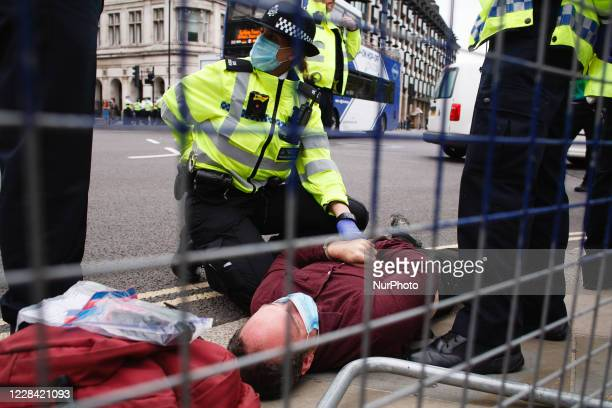 Police officers surround an arrested and handcuffed member of climate change activist movement Extinction Rebellion in Parliament Square in London,...