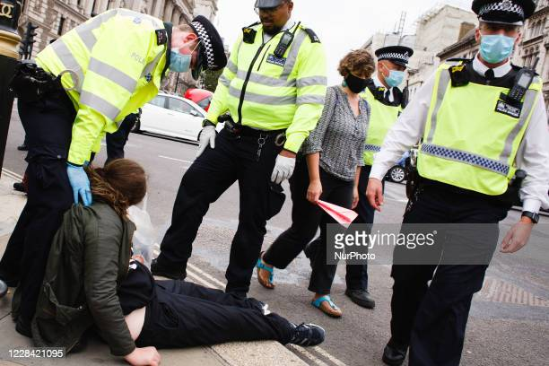 Police officers surround an arrested member of climate change activist movement Extinction Rebellion in Parliament Square in London, England, on...