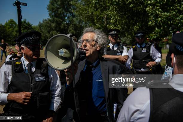 Police officers surround Piers Corbyn, brother of former Labour Party leader Jeremy Corbyn, before arresting him during a demonstration against the...