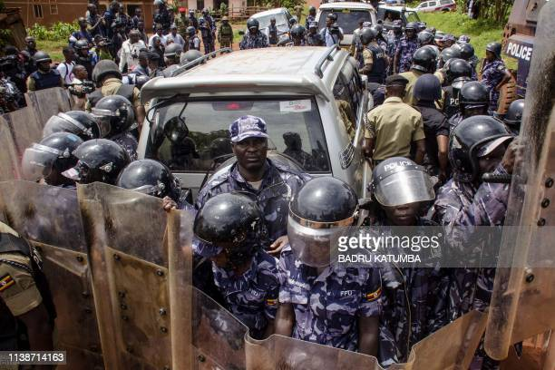 TOPSHOT Police officers surround the car of Ugandan musician turned politician Robert Kyagulanyi commonly known as Bobi Wine before his arrest on his...