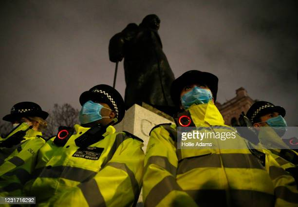 Police officers surround the statue of Winston Churchill on Parliament Square during a protest criticising the actions of the police at last night's...