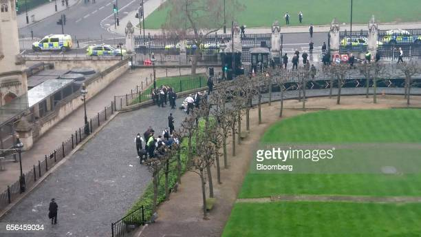 Police officers surround two individuals on the ground inside the gates of the Houses of Parliament near the entrance left in London UK on Wednesday...