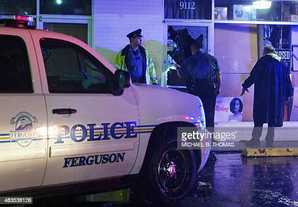 Police officers survey the damage after a local business was burglarized and looted during a protest march on West Florissant Avenue in Ferguson...