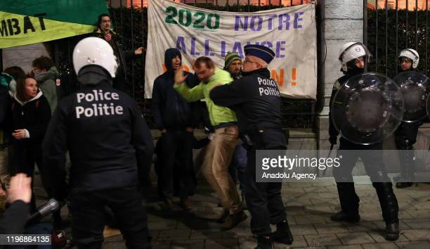 Police officers take a demonstrator into custody during a protest against briefing meeting on World Economic Forum to be held in Brussels Belgium on...
